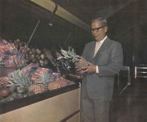 Carlton K. Mack inspects a pineapple at the Marabella store