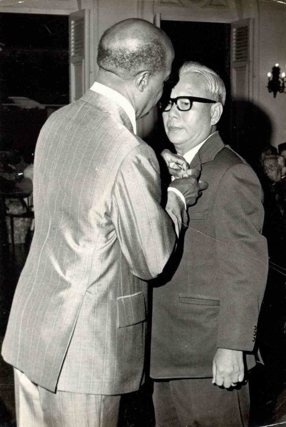 Carlton K. Mack receiving the Humming Bird Medal (Gold) from the Governor General Sir Ellis Clarke in 1975 who later became Trinidad & Tobago's first President